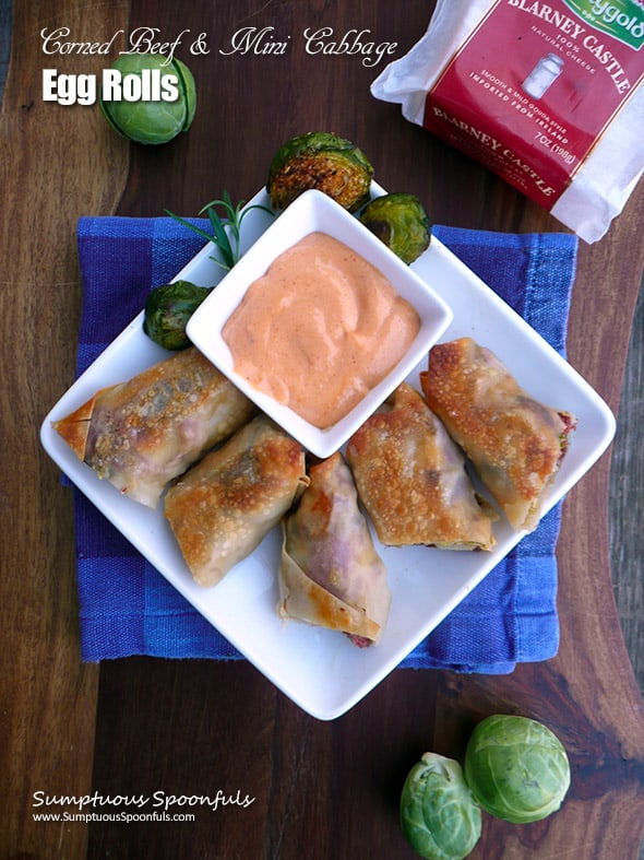 A plate of corned beef ande cabbage egg rolls with sauce.
