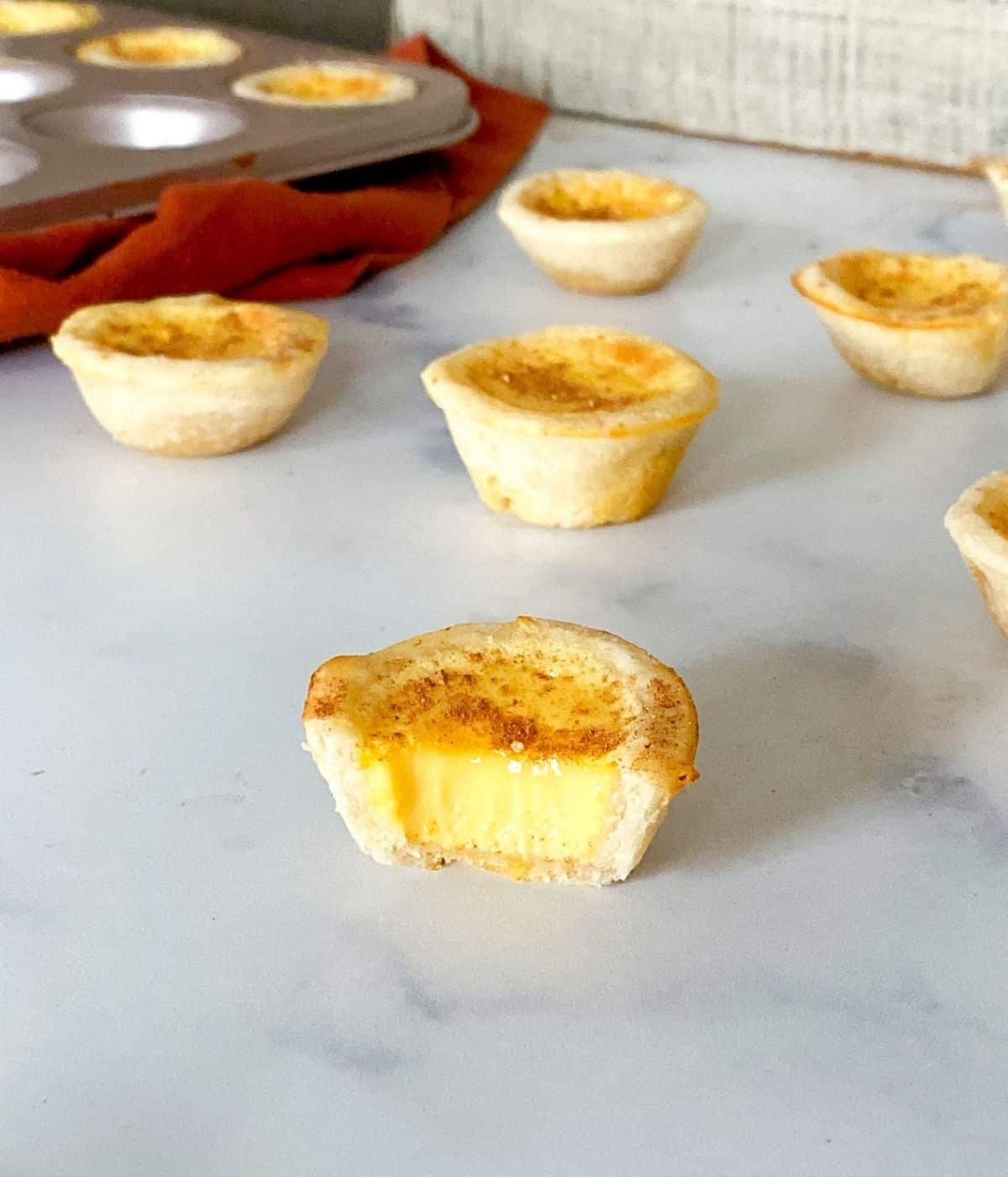 Mini egg custard tartlets on table with nutmeg.