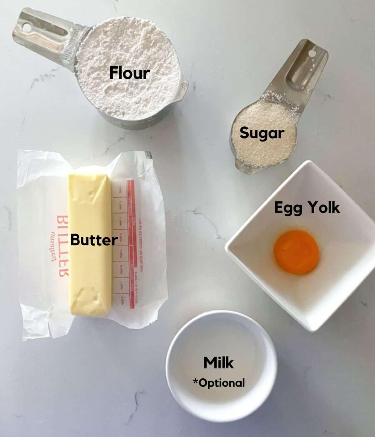 Egg custard tartlet dough ingredients on a table including flour, sugar, butter, egg yolks and milk.