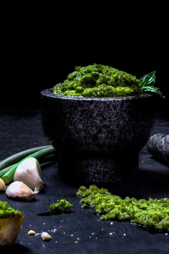 green garlic scape pesto in a mortar with garlic on the side.