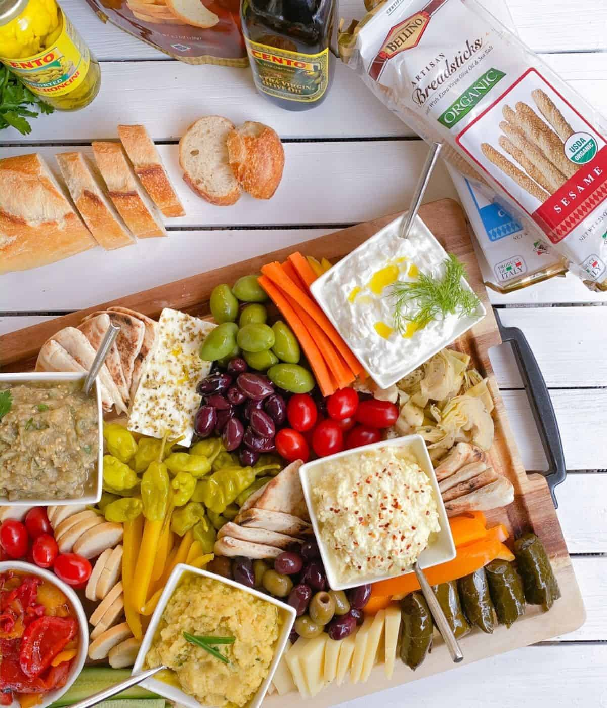 Greek mezze appetizers on a wooden cutting board with spreads and dips.