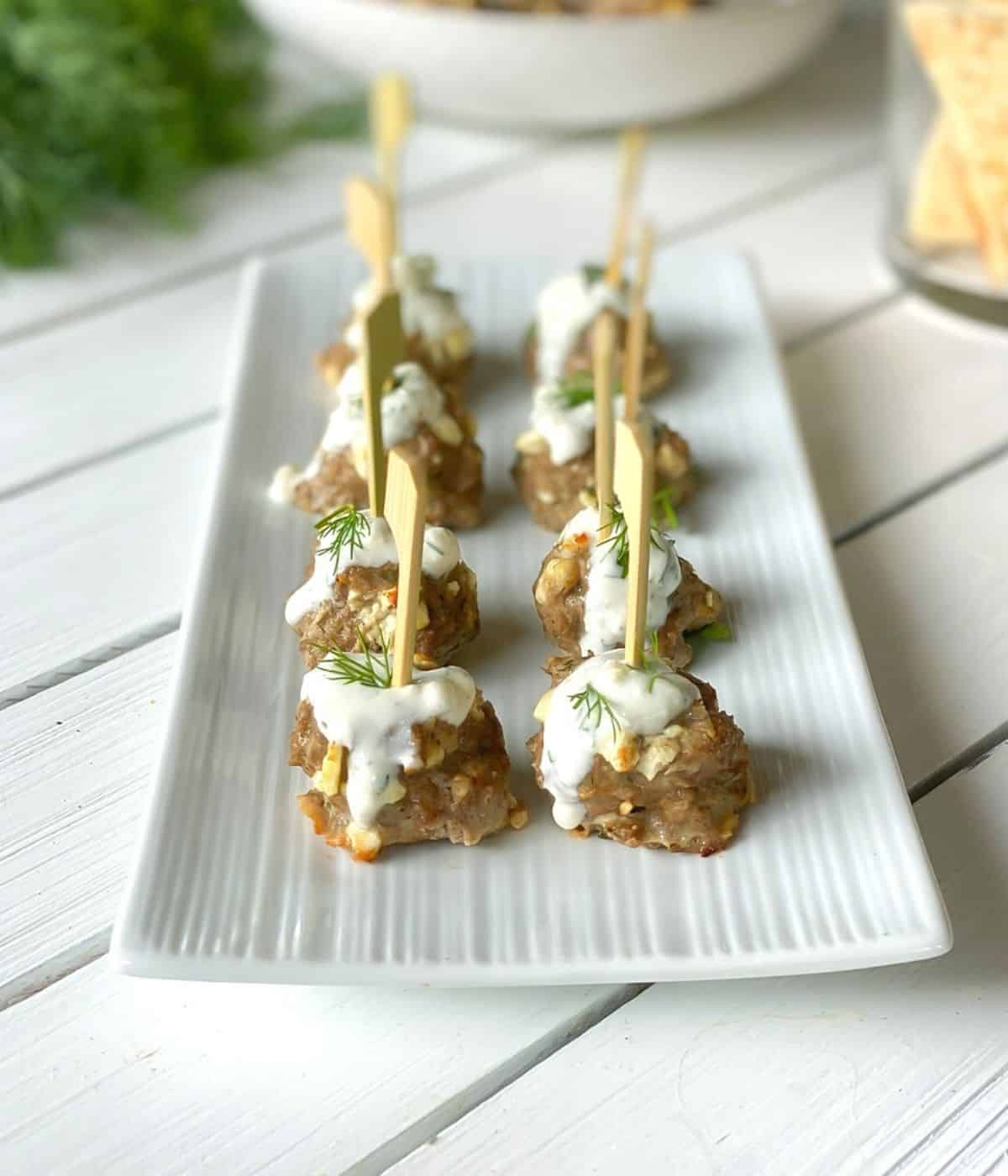 Skewered lamb and feta cheese meatballs on a plate with tzatziki sauce.