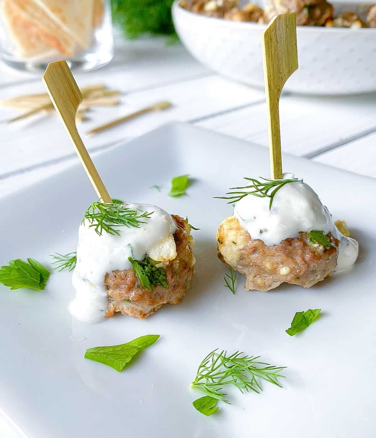 Greek lamb meatball appetizers on skewers with tzatziki sauce.