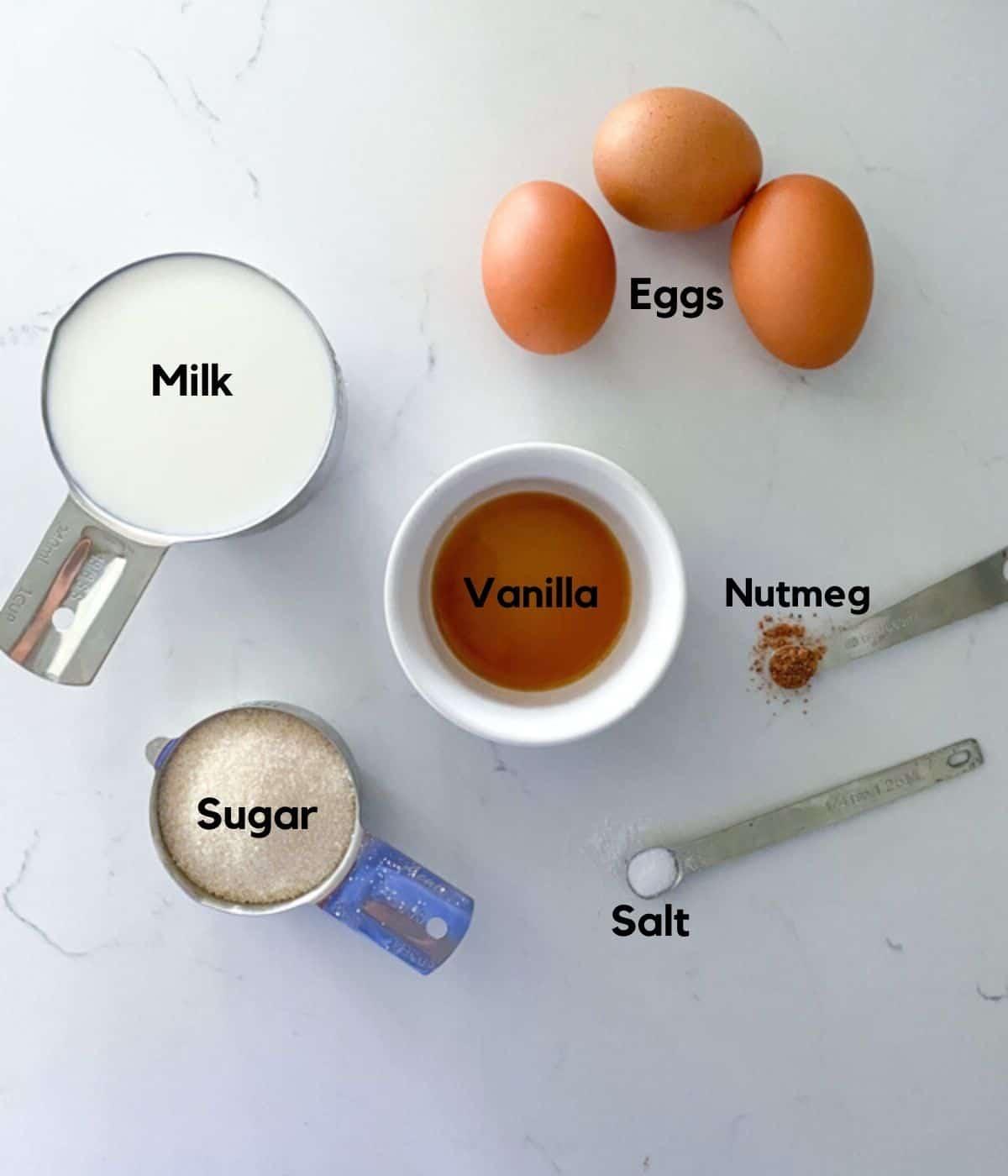Egg custard tart ingredients on a table including vanilla, sugar, nutmeg, eggs, milk and salt.