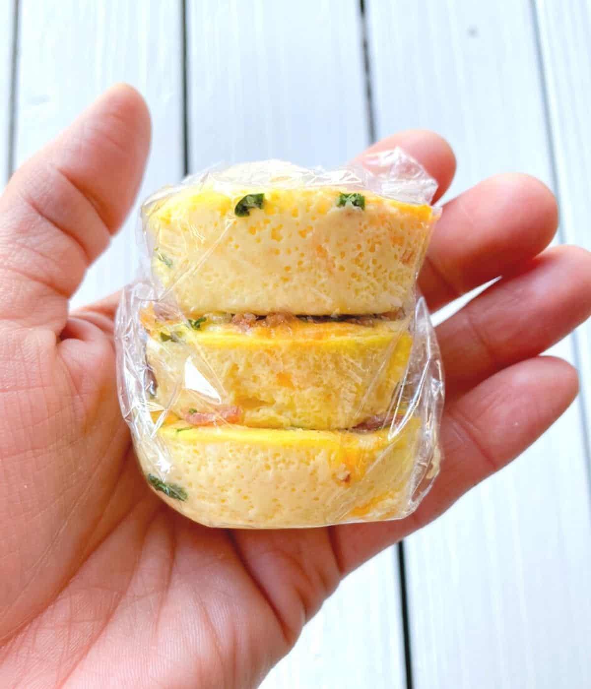 Starbucks copycat egg bites hand stacked inside plastic wrap.