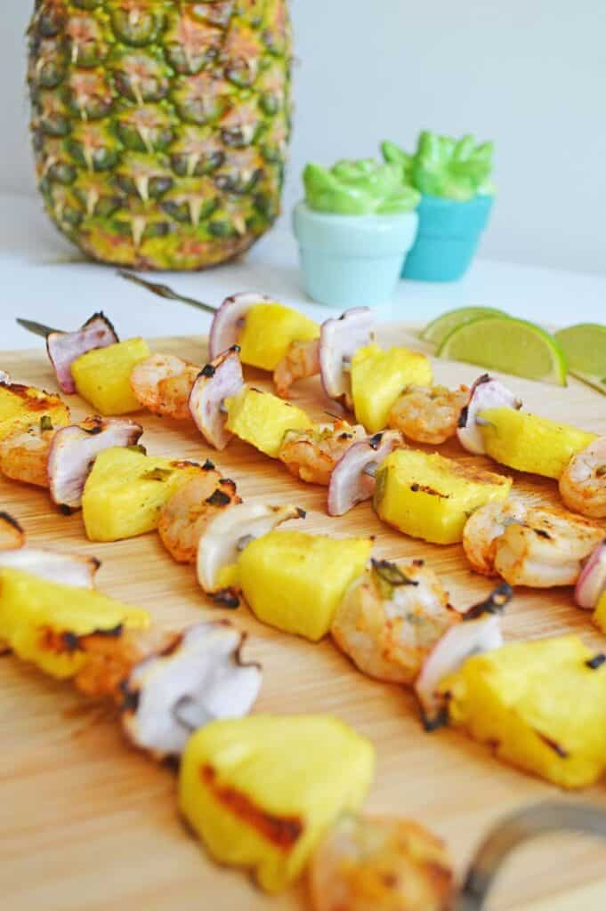 Cooked skewers of pineapple, chicken and onion on wooden cutting board with a garnish of lime slices.
