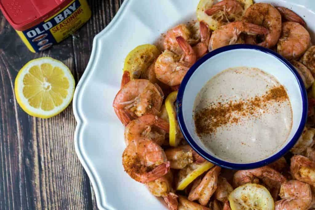 Blue rimmed bowl with dipping sauce surrounded by shell on shrimp on a large white platter.