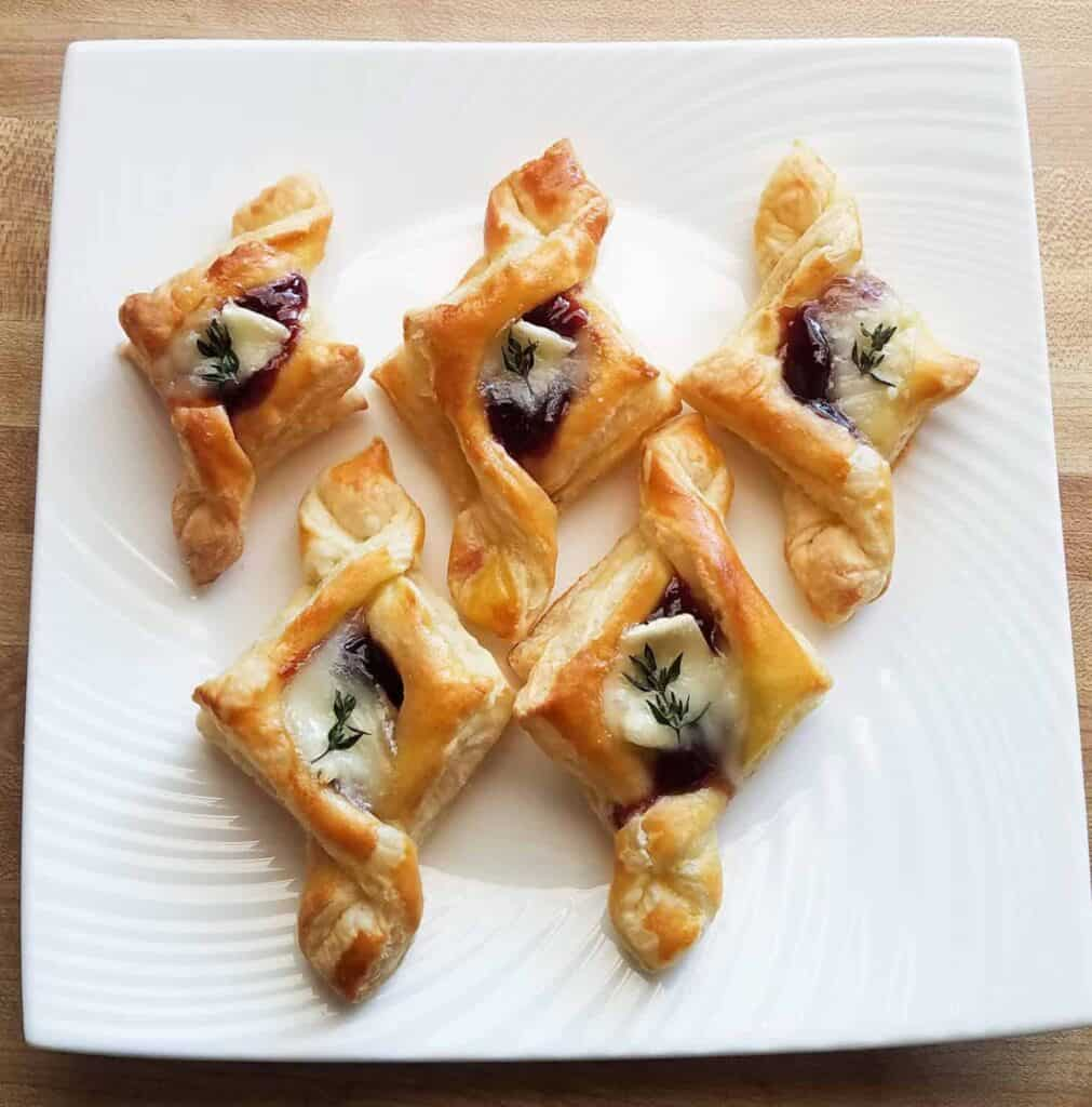 Five diamond shaped tarts with a raspberry and brie filling on a square white plate.