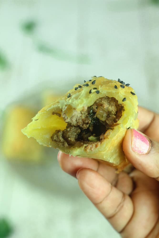 A hand holding an open pastry showing the meat filling with black sesame seed sprinkled on top.