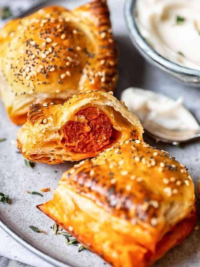 A view of the inside of a chorizo sausage roll on a sliver platter with a couple of whole rolls with sesame seed sprinkled on top.
