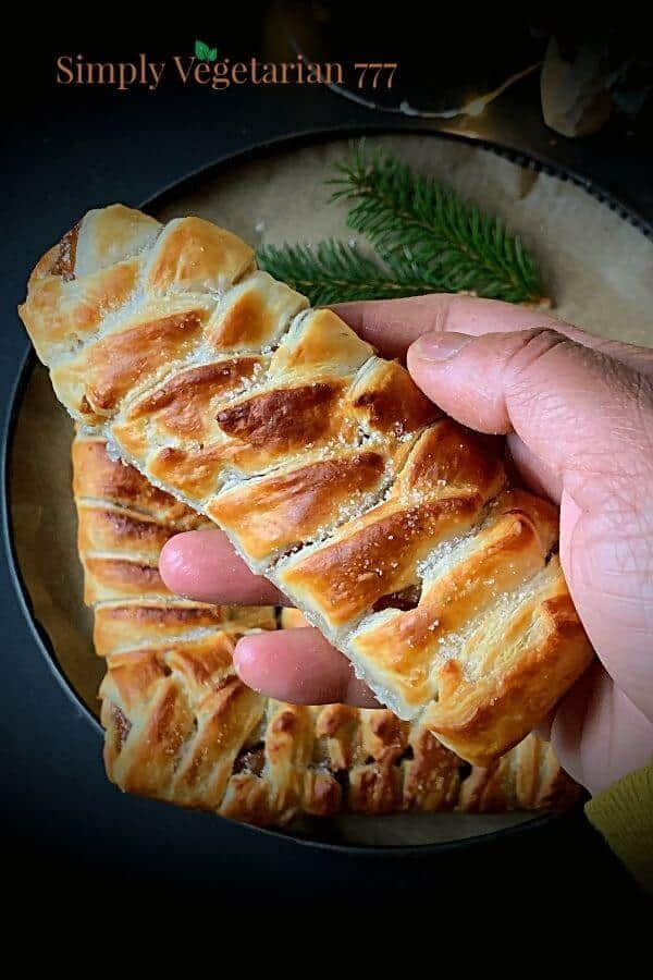 Someone holding an apple strudel above a tray of apple strudels and a green garnish.