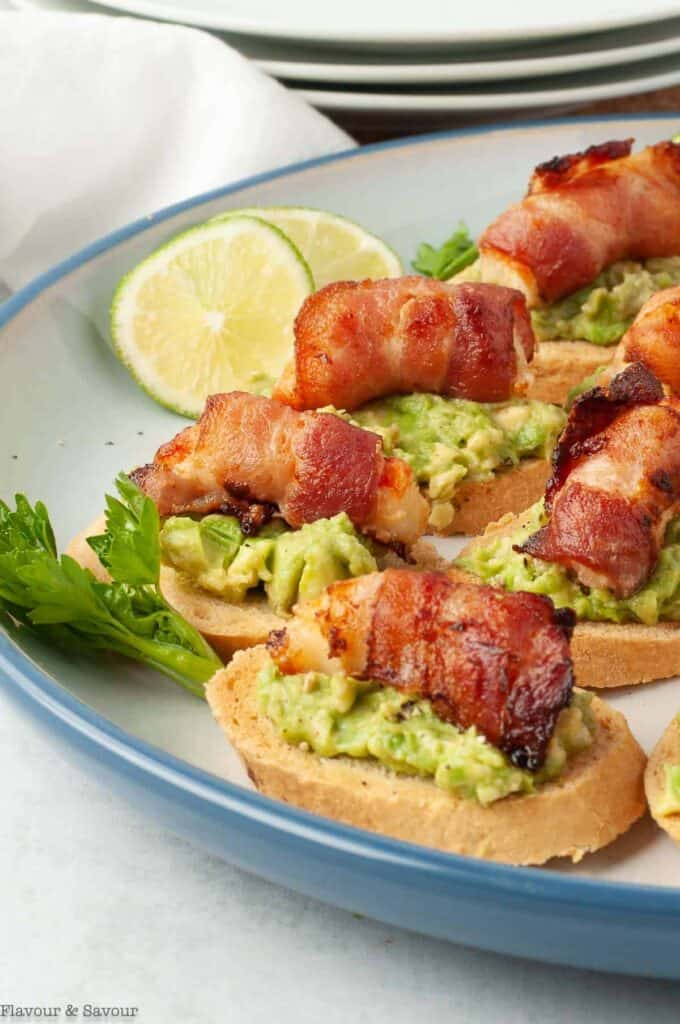 Bacon wrapped shrimp on top of avocado toast garnished with lemon and celery on a blue rimmed bowl.