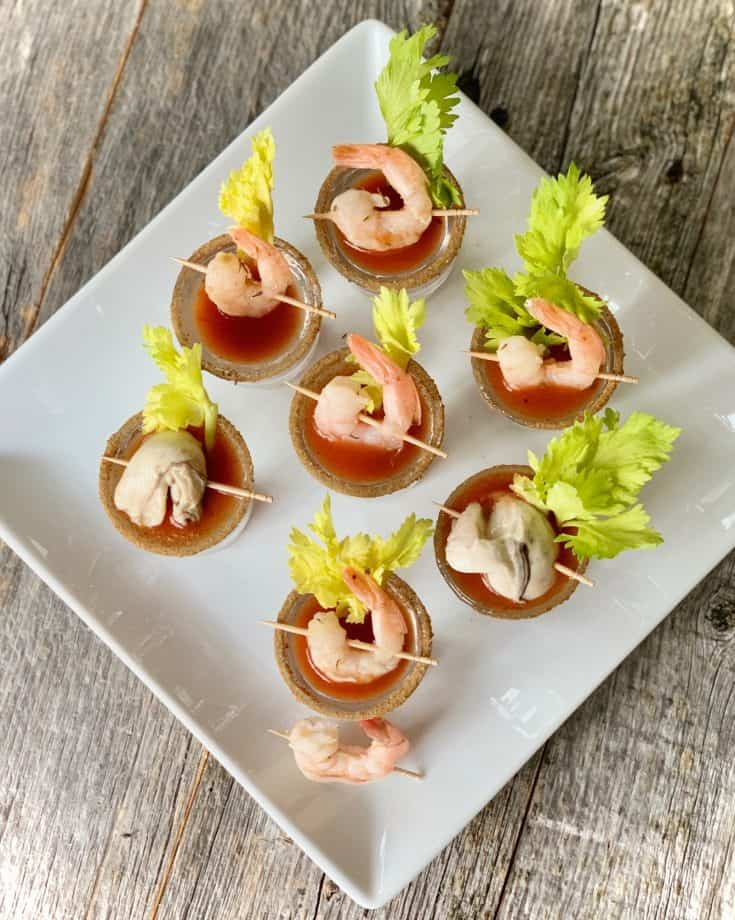 Top view of shot glasses filled with bloody mary mix and topped with a shrimp or oyster and a celery stick on a white square plate.