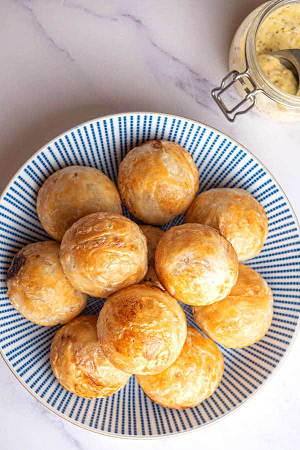 Top view of chicken pastry balls piled on a blue and white striped dish.