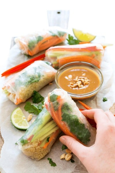 4 spring rolls on a wrapper with a clear bowl of peanut dipping sauce and a lime wedge garnish.
