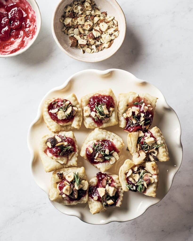 Cranberry puff pastry bites on a fluted white dish with a bowl of almonds and a bowl of red jam in the background.
