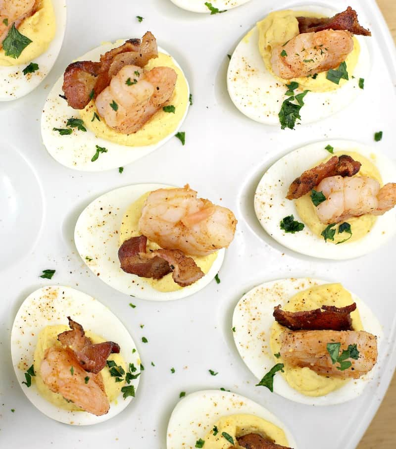 Deviled eggs topped with cooked shrimp and a piece of fried bacon on a white tray.