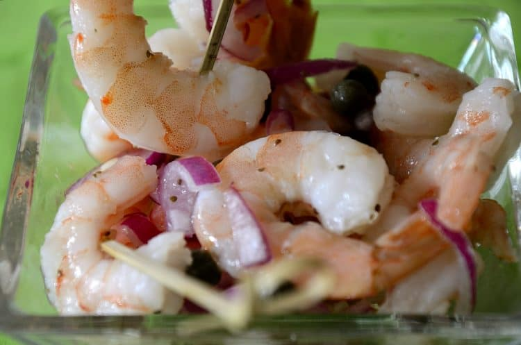 Cooked shrimp in a clear bowl on sticks with a red onion garnish.