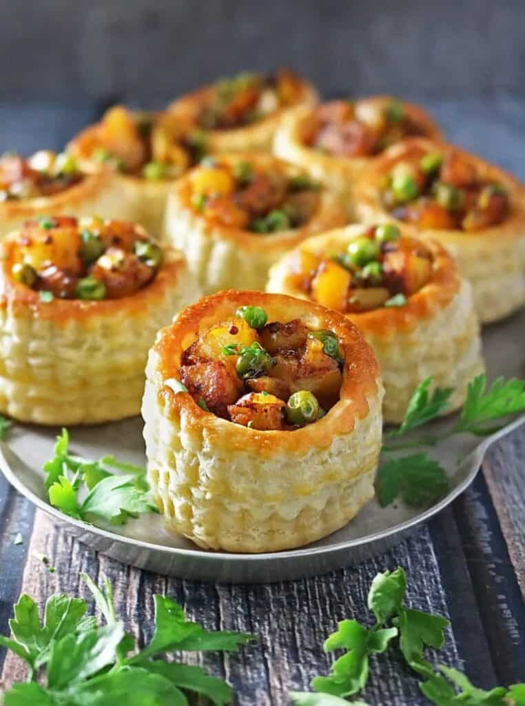 A silver tray filled with round pastries filled with a spiced potato mixture with a green garnish.