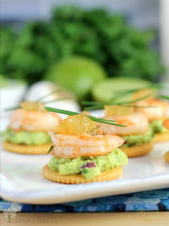 A white plate of crackers with guacamole, a cooked shrimp and pineapple preserves layered on top.
