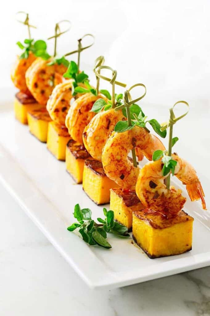 A row of cubes of butternut squash with shrimp skewered through them on a rectangle white plate.