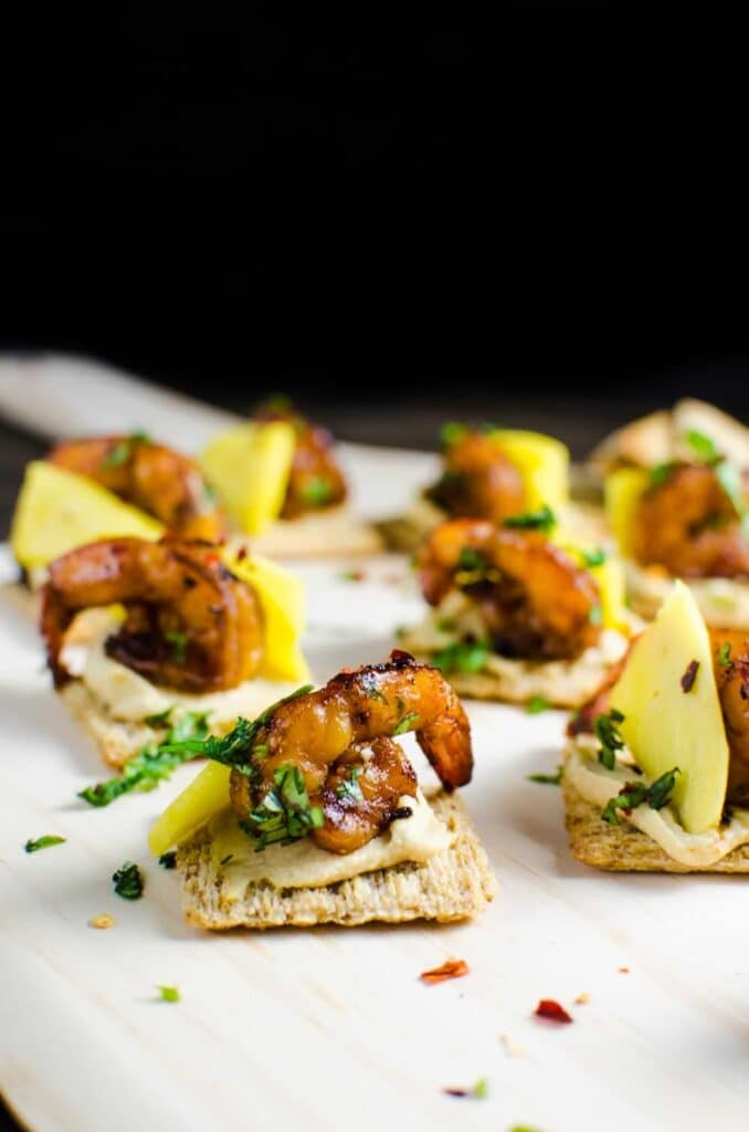 Crackers with hummus, shrimp and mango on a wood background.