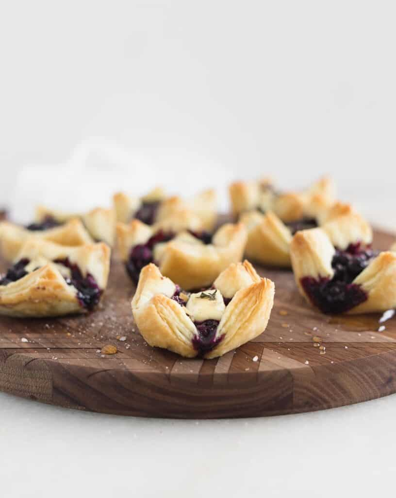 Blueberry brie bites on a round wooden cutting board.