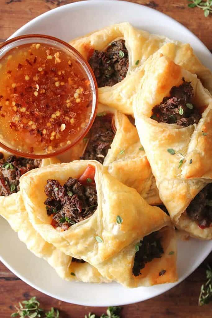 Stack of beef wellington turnovers on a white plate with a small bowl of sauce next to it.