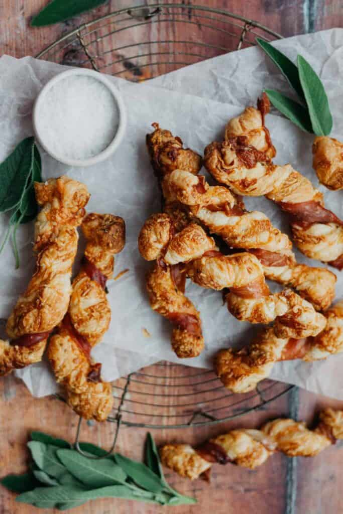 A pile of puff pastry twists on a withe paper on a wire rack with leaf garnish and and a small white bowl of salt.