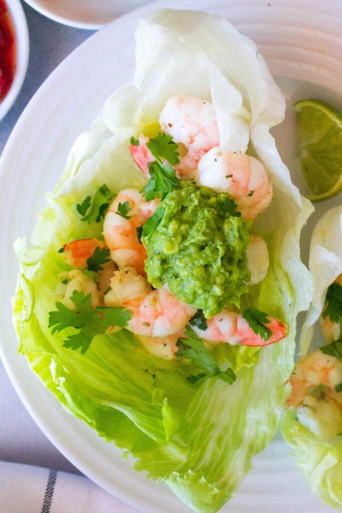 A lettuce wrap filled with shrimp avocado and cilantro.