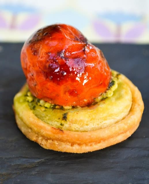 A small round puff pastry with a layer of pesto and a roasted cherry tomato on top.