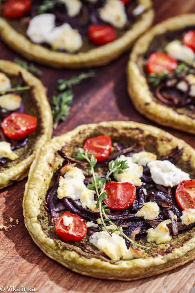 Tarts with purple onion, roasted cherry tomatoes, cheese and a sprig of thyme.
