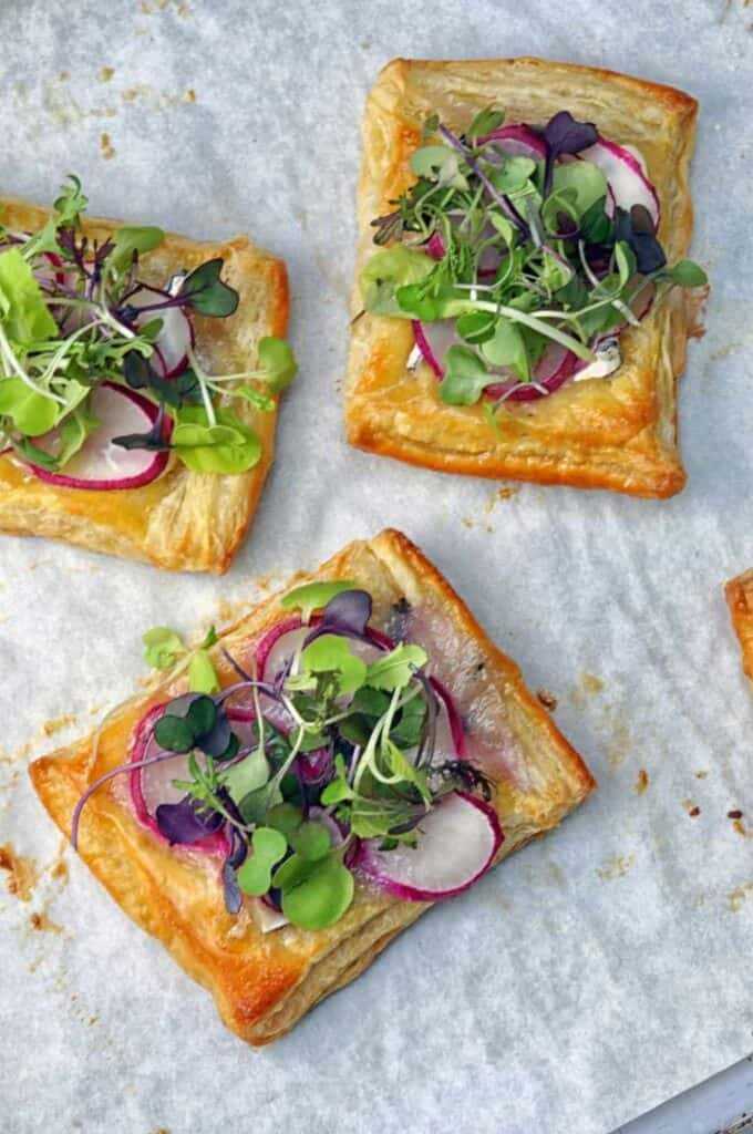 Three puff pastry squares with radish and greens on top.