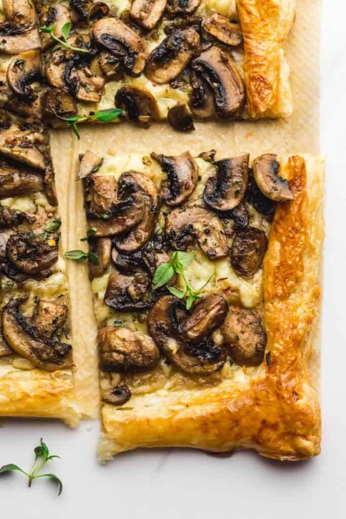 Mushroom tart on a white background with a piece cut out.