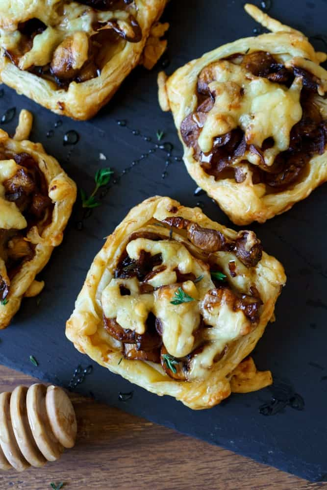 Square puff pastry tarts with gouda, mushrooms, and honey on a black surface with a wooden honey spoon laying next to them.