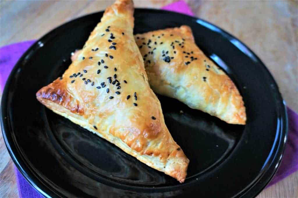 Two paneer puff pastry turnovers on a black dish.