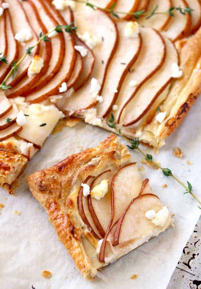 A pear and goat cheese tart garnished with fresh thyme and honey with a piece cut apart.