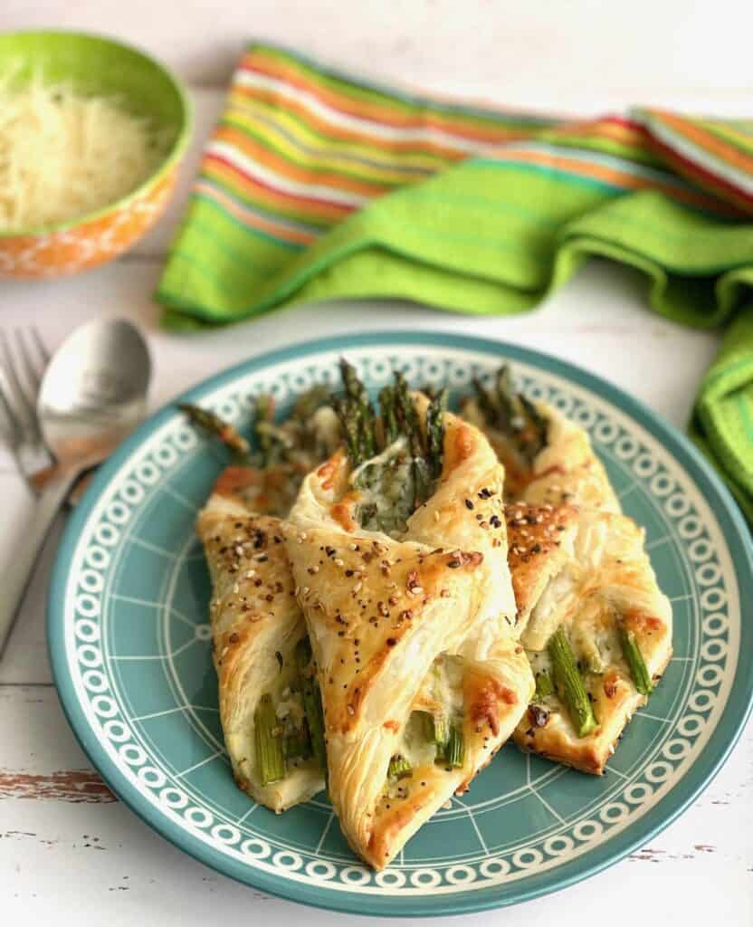 Puff pastry folded around asparagus spears with sesame seeds on top sitting on a blue patterned plate with a fork and spoon sitting next to it.