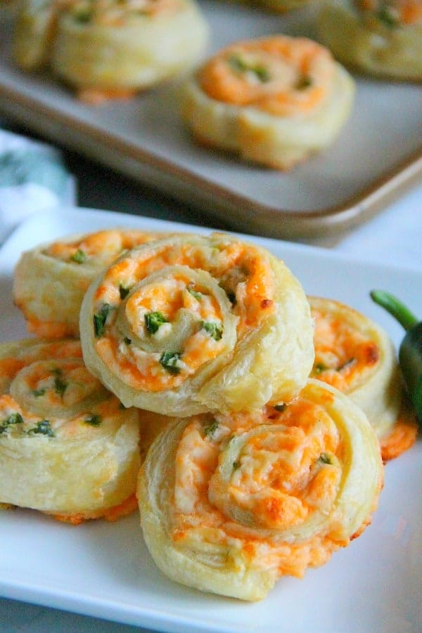 Stack of puff pastry pinwheels with cheese and jalapeno peppers on a white plate with a jalapeno next to them.