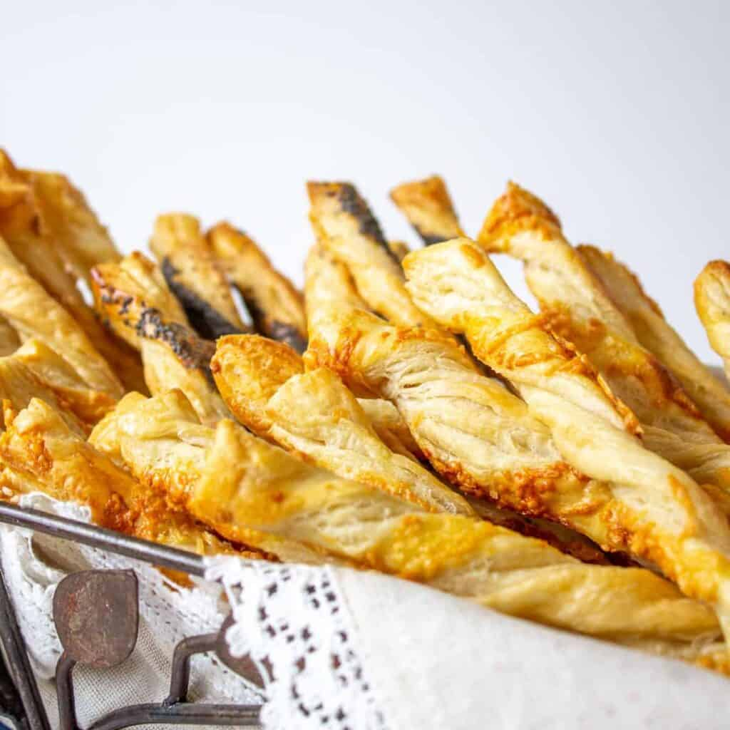 A pile of cheese straws in a wire basket lined with a white linen.