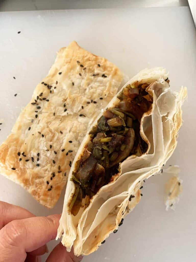 A view of the filling inside a bakleh with a whole one next to it and garnished with black sesame seeds.