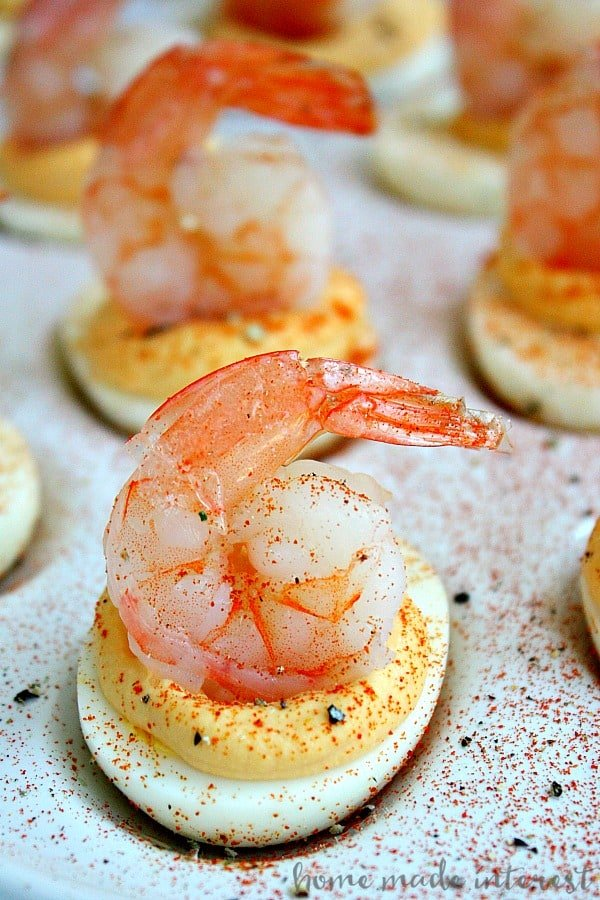 Deviled eggs with shrimp on top with spices sprinkled over them on a white tray.