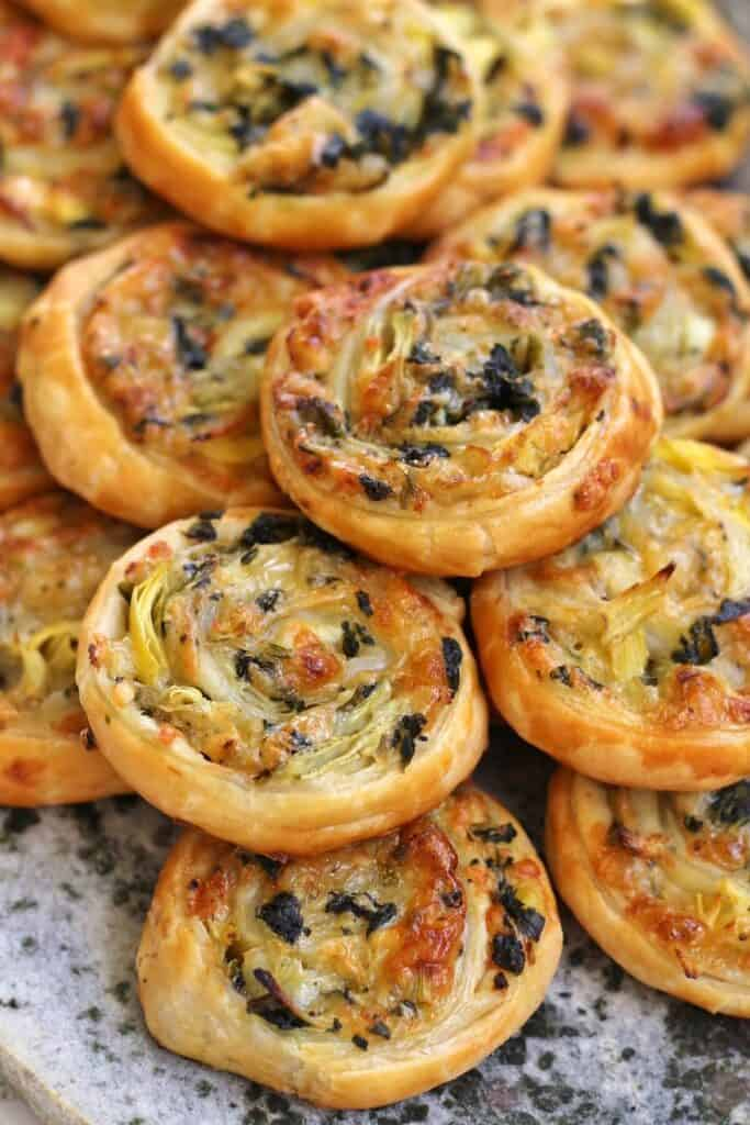 A stack of baked spinach and artichoke pastry swirls appetizers.