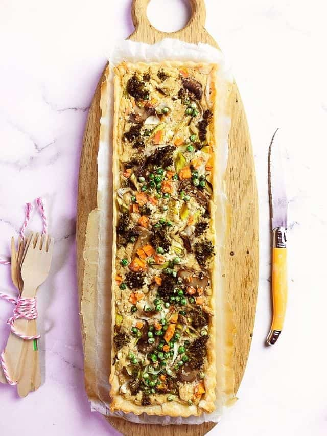A tart with peas, carrots and other roasted vegetables on a wooden cutting laying on a marble counter with a knife and wooden forks laying next to it.