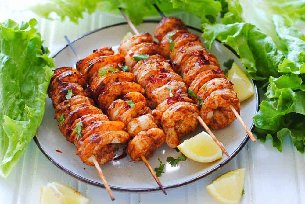 4 shrimp skewers laying on a white plate with lemon wedges.