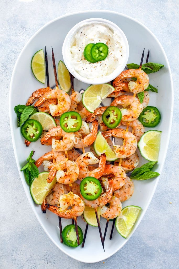 Cooked skewers of tequila jalapeno on a white plate next to a small white bowl with a white dip garnished with lime jalapeno slices.