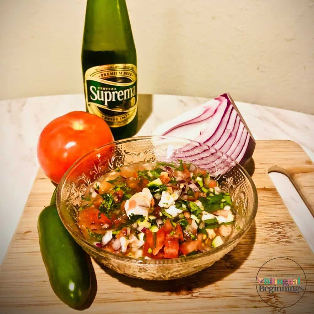 Ceviche in a crystal bowl on a wooden cutting board with a tomato and a jalapeno pepper.
