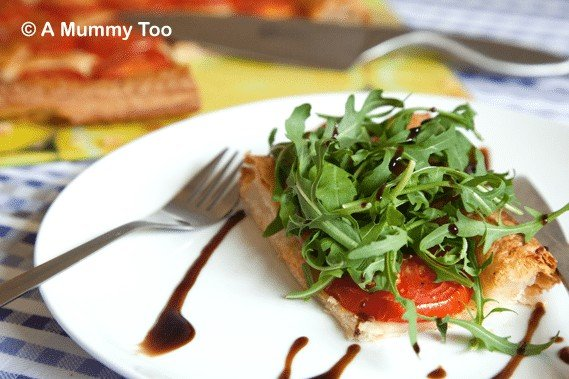 A round white plate with a square of puff pastry with a tomato and green on top drizzled with balsamic vinegar.