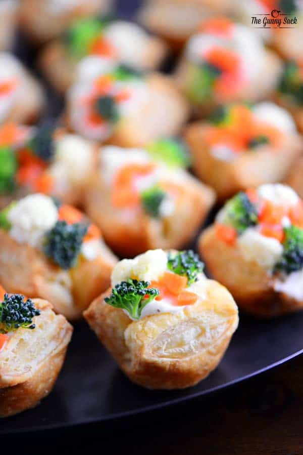 A blue tray of veggie pizza puffs with carrots, cauliflower, and broccoli on top of puff pastry bites.