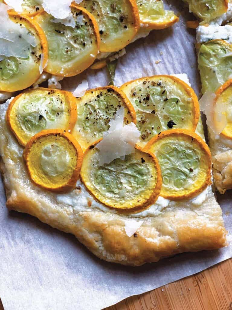 A piece of around tart with yellow squash and cheese shreds on top.